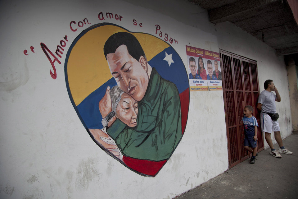"A heart-shaped mural shows an image of Venezuela's President Hugo Chavez hugging a woman in Caracas, Venezuela, Friday, Jan. 4, 2013. Chavez hasn't spoken publicly or been seen since his Dec. 11 operation in Cuba, and the latest report from his government Thursday night increased speculation that he is unlikely to attend his Jan. 10 inaugural ceremony. The message above the mural reads in Spanish; ""Love is repaid with love."" (AP Photo/Ariana Cubillos)"