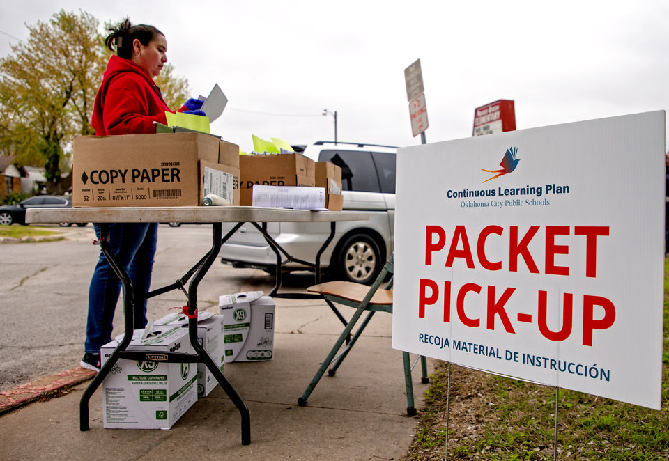 Photo - Prairie Queen Elementary teacher Veronica Ramirez prepares to handout distant learning packets at the school in Oklahoma City, Okla. on Monday, April 6, 2020. Oklahoma City Public Schools and other districts across the state began their first day of handing out the distant learning packets.    [Chris Landsberger/The Oklahoman]