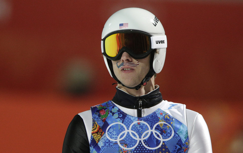 Photo - United States' Nicholas Alexander sports a mustache-shaped American flag painted on his face during the ski jumping large hill team competition at the 2014 Winter Olympics, Monday, Feb. 17, 2014, in Krasnaya Polyana, Russia. (AP Photo/Matthias Schrader)