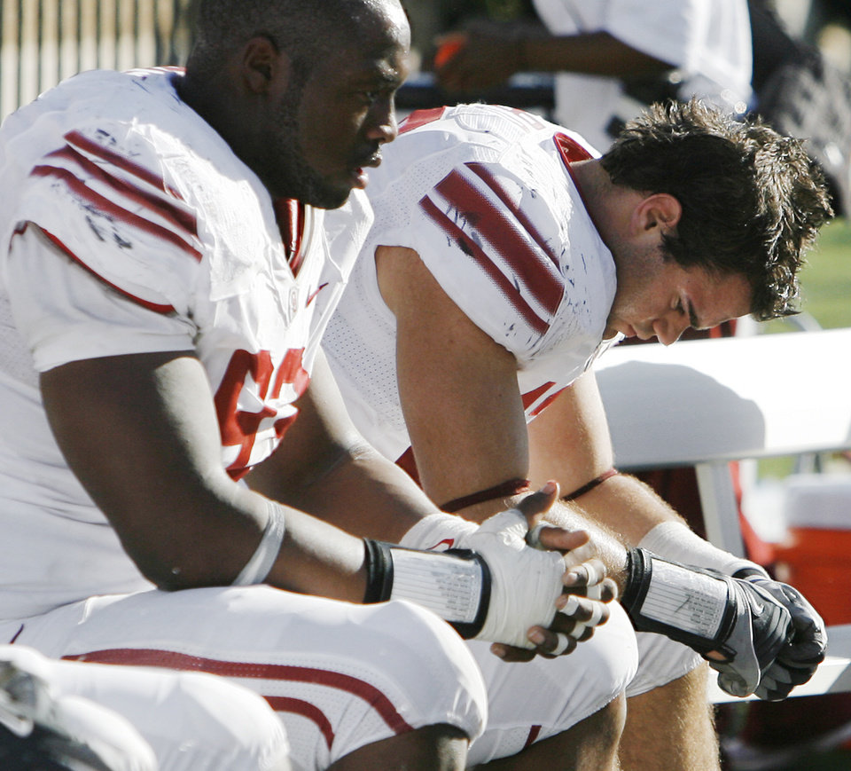 Photo - OU's Gerald McCoy (93), left, and Austin Box (12) sit on the bench late in the fourth quarter during the college football game between the University of Oklahoma Sooners (OU) and the Texas Tech University Red Raiders (TTU) at Jones AT&T Stadium in Lubbock, Texas, Saturday, Nov. 21, 2009. Texas Tech won, 41-13. Photo by Nate Billings, The Oklahoman