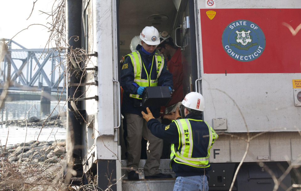 Photo - In this Dec 1, 2013 photo provided by the National Transportation Safety Board,  NTSB investigator George Haralampopoulous hands a data recorder down to Mike Hiller from the derailed Metro-North train in the Bronx borough of New York. Two data recorders from the commuter train that derailed while rounding a riverside curve, killing four people, may provide information on the speed of the train, how the brakes were applied and the throttle setting, a member of the NTSB said Monday. The NTSB was downloading data from a recorder previously found in the rear locomotive in the train that derailed Sunday in New York. A second recorder was found in the front car of the train and has been sent to Washington for analysis, NTSB board member Earl Weener said. (AP Photo/NTSB)