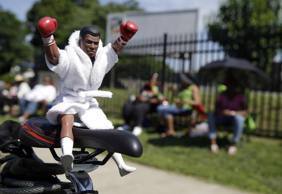 Photo - A Muhammad Ali action figure sits on the seat of a bicycle as fans await the funeral procession for the late boxing champion to make its way down Muhammad Ali Boulevard in Louisville, Ky. Friday, June 10, 2016. (AP Photo/Michael Conroy)