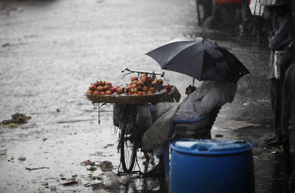 An Indian fruit vendor shields himself with an umbrella during a sudden rain shower in Hyderabad, India, Tuesday, April 2, 2013. (AP Photo/Mahesh Kumar A.)