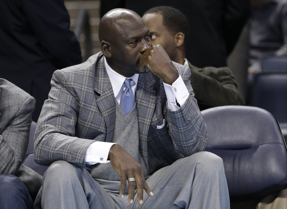 Photo - FILE - In this Jan. 23, 2013 file photo, Charlotte Bobcats owner Michael Jordan looks on from courtside during the second half of an NBA basketball game between the Charlotte Bobcats and the Atlanta Hawks in Charlotte, N.C. An Atlanta woman has filed a lawsuit saying basketball Hall of Famer and Charlotte Bobcats owner Michael Jordan is the father of her teenage son. The lawsuit was filed Feb. 6 by Pamela Smith in Fulton County Superior Court.  (AP Photo/Chuck Burton, File)