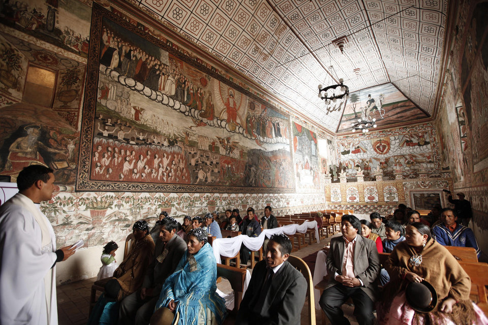 Father Gabriel Antequera celebrates a wedding in the Sistine Chapel of Los Andes in Curahuara de Carangas, Oruro department, 260 km. (160 miles) south from La Paz, Bolivia, Saturday, Dec. 8, 2012.  The colonial-era house of worship known in Bolivia as the Sistine Chapel of the Andes was filled with flowers over the weekend for those celebrating two weddings and seven baptisms on the wind swept mountain plateau.(AP Photo/Juan Karita)