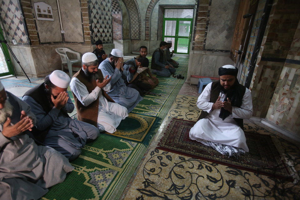 Photo -  Unmasked worshippers offer Friday prayers at a mosque during a lockdown to to help stop the spread of the coronavirus in Peshawar, Pakistan, March, 3, 2020. Some mosques were allowed to remain open in Pakistan on Friday, the Muslim sabbath when adherents gather for weekly prayers, even as the coronavirus pandemic spread and much of the country had shut down. (AP Photo/Muhammad Sajjad)
