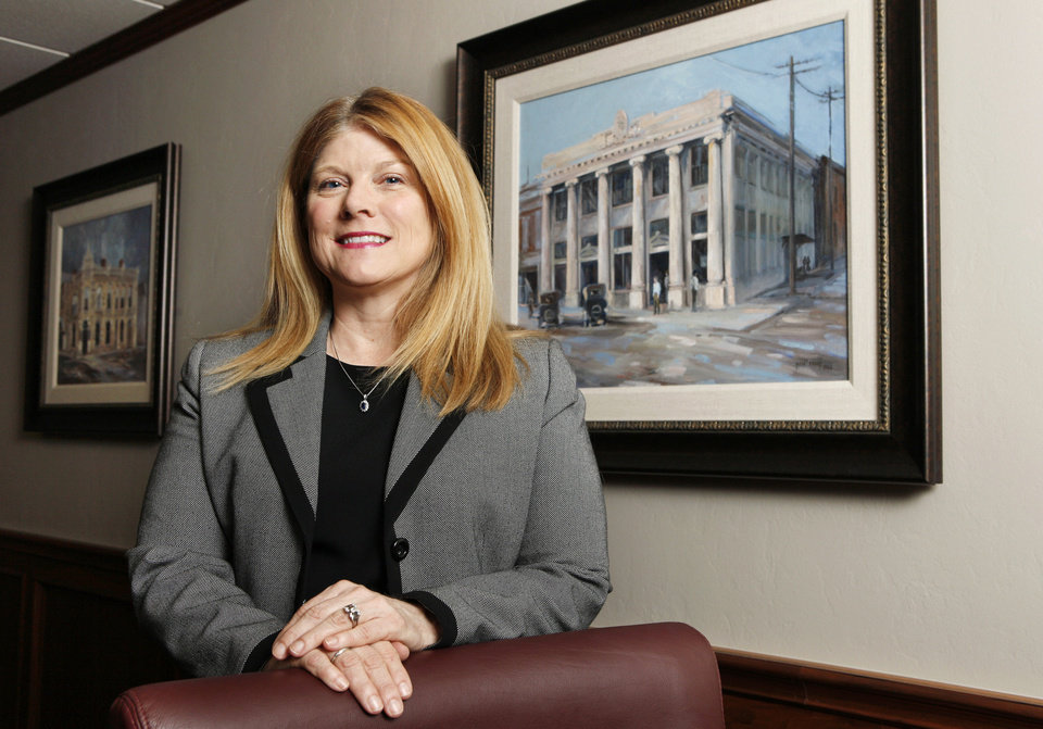Suzie Symcox, executive vice president and chief administrative officer of First Fidelity Bank, is shown Tuesday in the board room at First Fidelity Bank headquarters in Oklahoma City. The painting is First Fidelity's first bank in Norman shown as it appeared in August of 1920. Photo by Paul B. Southerland, The Oklahoman <strong>PAUL B. SOUTHERLAND</strong>