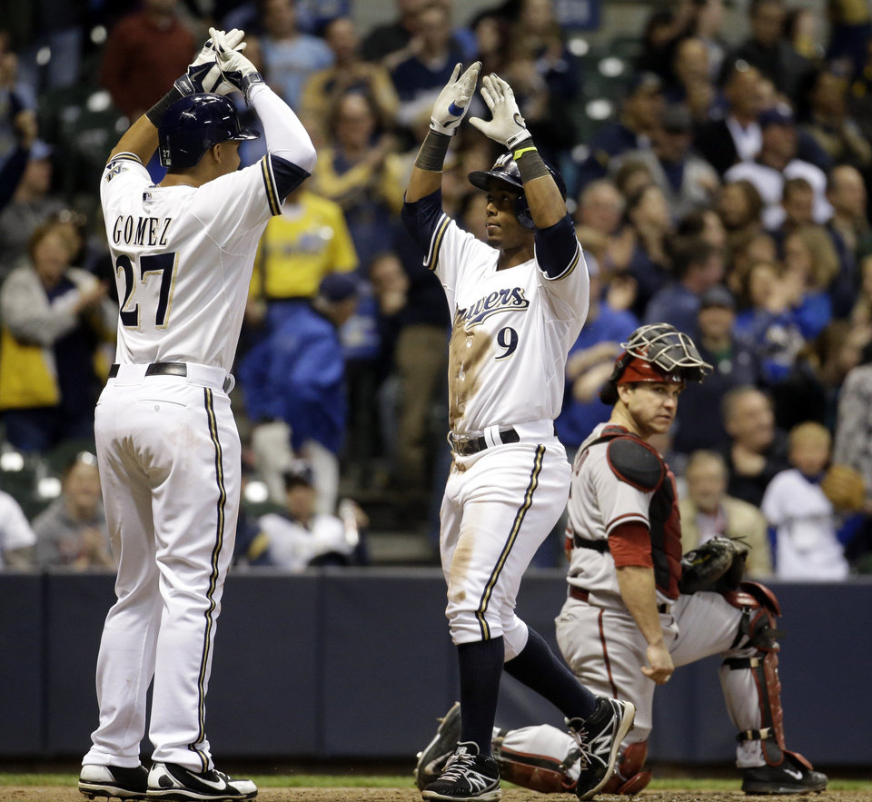 Photo - Milwaukee Brewers' Jean Segura celebrates with Carlos Gomez in front of Arizona Diamondbacks catcher Miguel Montero after Segura hit a two-run home run during the sixth inning of a baseball game Monday, May 5, 2014, in Milwaukee. (AP Photo/Morry Gash)