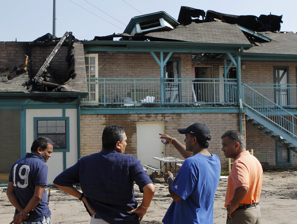 Friends of the owner of this business look at the aftermath of a pre-dawn blaze that destroyed the Stratford House Inns at 3020 S. Broadway in Edmond, Wednesday, May 30, 2012, Photo by Jim Beckel, The Oklahoman