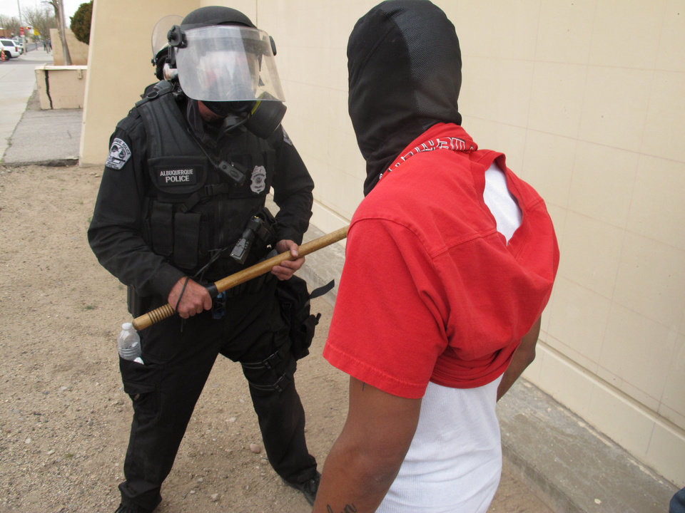 Photo - A protester faces off with an Albuquerque officer during a rally against recent police shootings in Albuquerque, N.M. on Sunday March 30, 2014. Hundreds of protesters marched past riot police in Albuquerque on Sunday, days after a YouTube video emerged threatening retaliation for a recent deadly police shooting. The video, which bore the logo of the computer hacking collective Anonymous, warned of a cyberattack on city websites and called for the protest march. (AP Photo/Russell Contreras)
