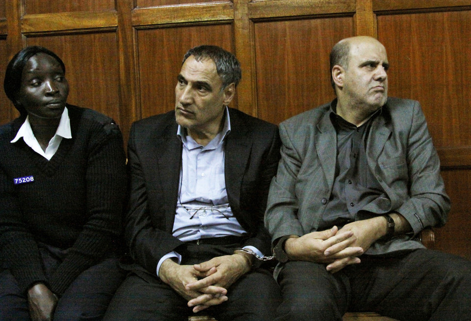 Photo -   FILE - In this Wednesday, June 27, 2012 file photo, a Kenyan policewoman accompanies Iranian nationals Sayed Mansour Mousavi, center, and Ahmad Abolfathi Mohammad, right, in the Nairobi magistrates court in Nairobi, Kenya, where they faced charges related to the possession of explosives. On Monday, July 2, 2012, officials told The Associated Press that Mousavi and Mohammad, who led authorities to a cache of explosives after their arrest, planned to attack Israeli, U.S., British or Saudi targets inside Kenya. (AP Photo/Khalil Senosi, File)