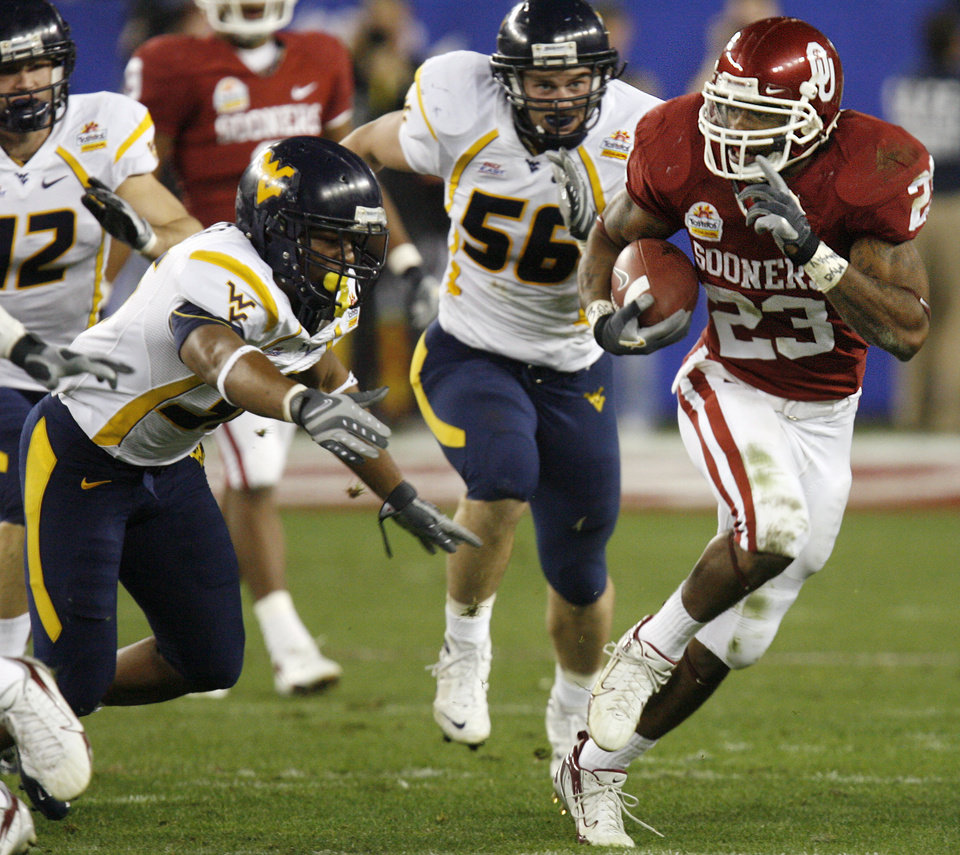 Photo - Oklahoma's Allen Patrick (23) takes the ball up field past the West Virginia defense during the first half of the Fiesta Bowl college football game between the University of Oklahoma Sooners (OU) and the West Virginia University Mountaineers (WVU) at The University of Phoenix Stadium on Wednesday, Jan. 2, 2008, in Glendale, Ariz. 