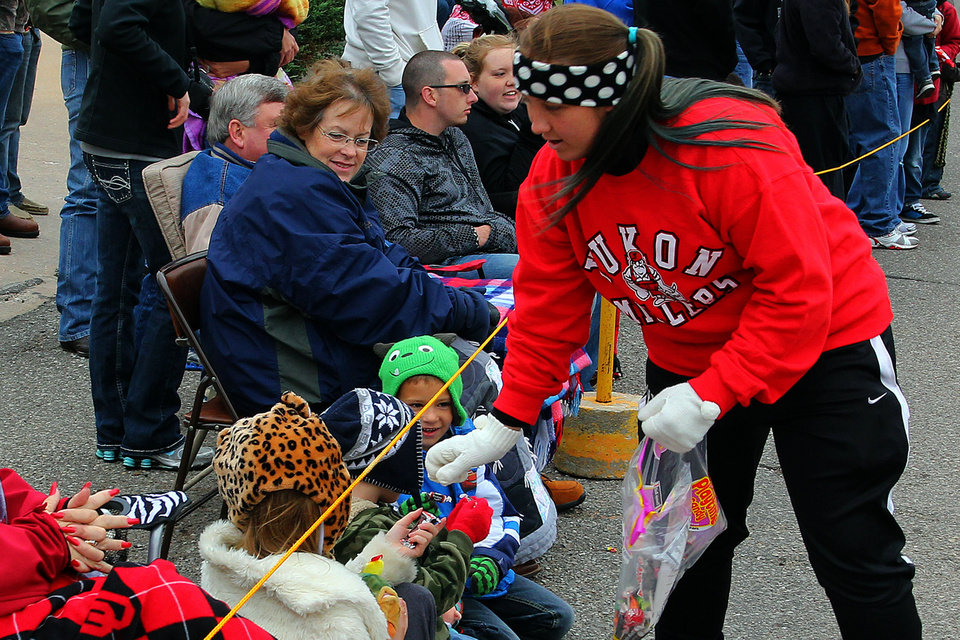 Photo - Kiley Wells passes out candy during the 47th annual Czech Festival parade Saturday in Yukon. PHOTO BY HUGH SCOTT FOR THE OKLAHOMAN
