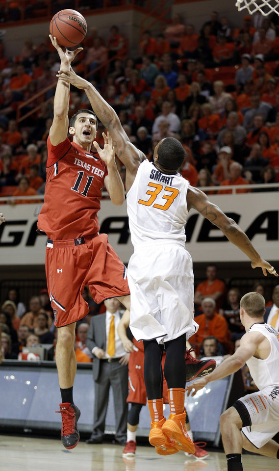 Photo - Oklahoma State's Marcus Smart (33) defends against Dejan Kravic (11) during the men's college basketball game between Oklahoma State and Texas Tech at Gallagher-Iba Arena in Stillwater, Okla., Saturday, Feb. 22, 2014. OSU won 84-62. 