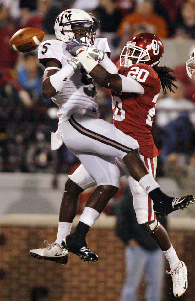 Photo - Oklahoma's Quinton Carter (20) breaks up a pass for Texas A&M's Howard Morrow (5) during the first half of the college football game between the University of Oklahoma Sooners (OU) and the Texas A&M Aggies at Gaylord Family-Memorial Stadium on Saturday, Nov. 14, 2009, in Norman, Okla. 