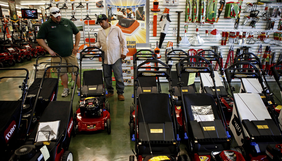 Teodoro Gonzalez, at right, gets help from Trey Hall while shopping for a lawn mower at O\'Connor\'s in Oklahoma City, Tuesday, March 13, 2012. Photo by Bryan Terry, The Oklahoman