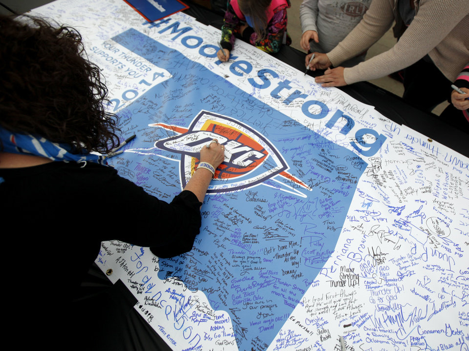 Photo - Fans sign a banner for Moore, Okla., before Game 5 of the Western Conference semifinals in the NBA playoffs between the Oklahoma City Thunder and the Los Angeles Clippers at Chesapeake Energy Arena in Oklahoma City, Wednesday, May 14, 2014. Photo by Bryan Terry, The Oklahoman