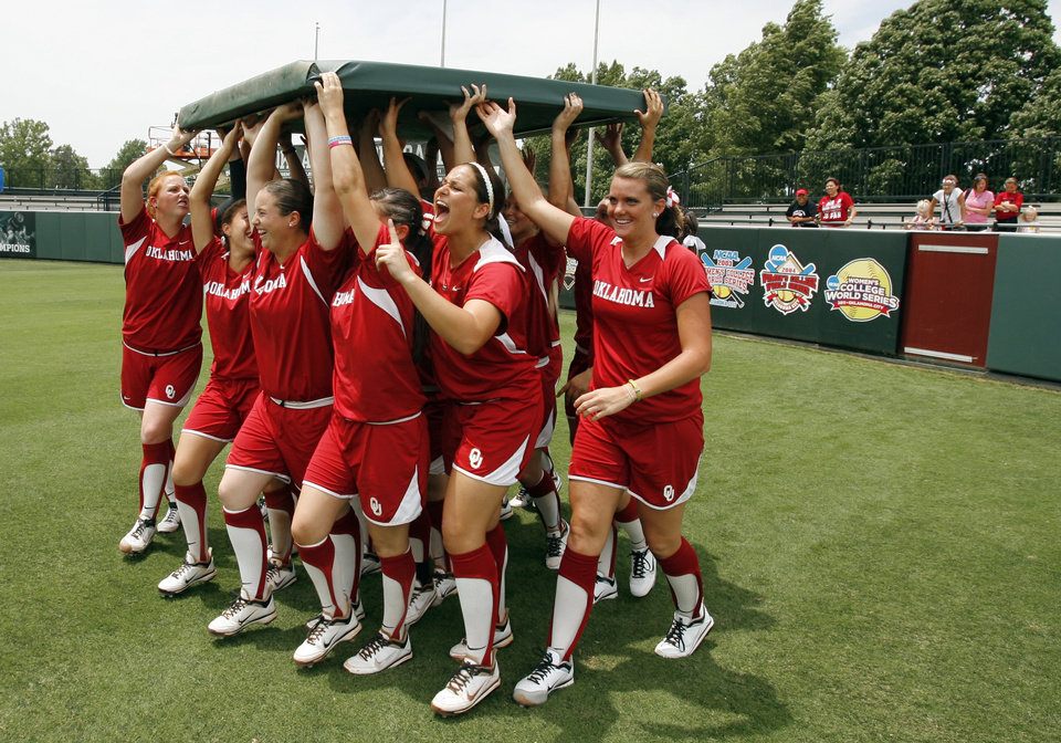 Photo - University of Oklahoma Sooner Softball team members remove a fence panel where they think the next win banner should go after defeating Arizona in game two of the NCAA Softball Norman Super Regional at Marita Hines field on Saturday, May 26, 2012, in Norman, Okla.  Photo by Steve Sisney, The Oklahoman