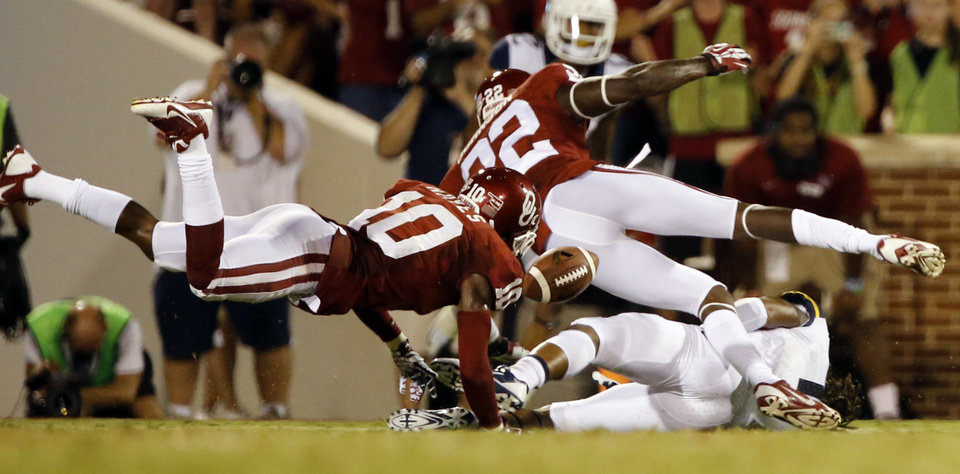 Photo - Quentin Hayes (10)  and Cortez Johnson (22) knock the ball from runner Kevin White (11) allowing Gabe Lynn (9)  to pick up the fumble during the second half of a college football game between the University of Oklahoma Sooners (OU) and the West Virginia University Mountaineers at Gaylord Family-Oklahoma Memorial Stadium in Norman, Okla., on Saturday, Sept. 7, 2013. Photo by Steve Sisney, The Oklahoman