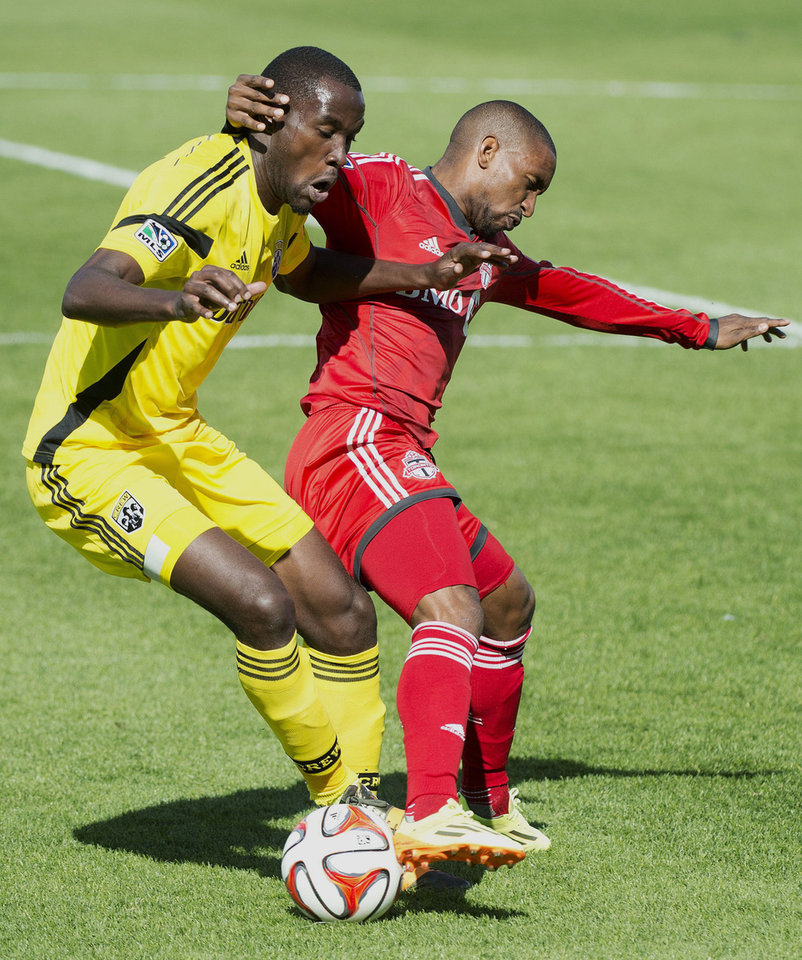 Photo - Toronto FC forward Jermain Defoe, right, battles for the ball against Columbus Crew midfielder Tony Tchani, left, during first half MLS soccer action in Toronto on Saturday May 31, 2014. (AP Photo/The Canadian Press, Nathan Denette)