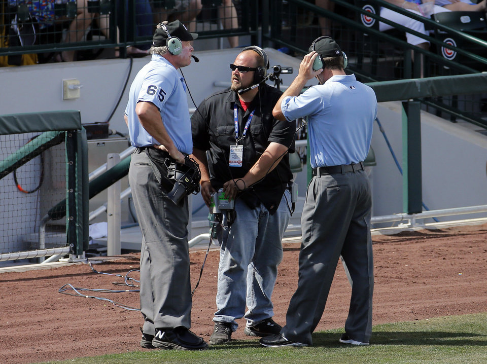 Photo - Umpires Ted Barrett (65) and Todd Tichenor, right, listen to the instant replay booth to decide whether a double hit by Los Angeles Angels Josh Hamilton was a home run, against the Chicago Cubs during the third inning of a spring training baseball game, Tuesday, March 25, 2014, in Mesa, Ariz. The hit was ruled a double after replay. (AP Photo/Matt York)
