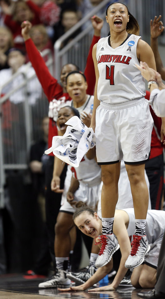 Photo - Louisville guard Antonita Slaughter (4) cheers from the bench after a Louisville basket during the first half of a regional semifinal game against LSU at the NCAA college basketball tournament on Sunday, March 30, 2014, in Louisville, Ky. (AP Photo/John Bazemore)