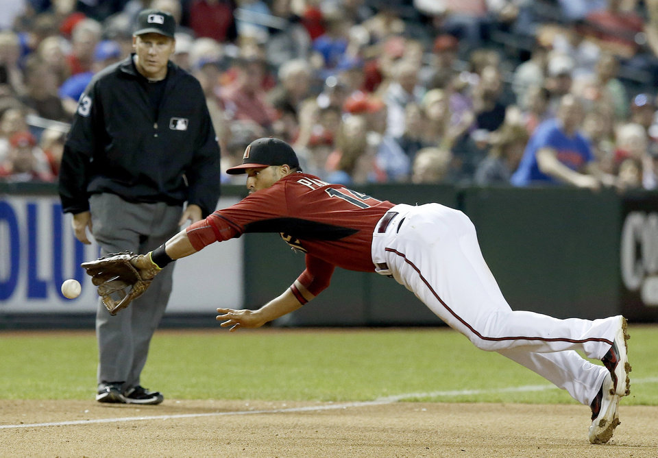 Photo - Arizona Diamondbacks' Martin Prado, right, makes a diving stop on a ground ball by Chicago Cubs' Darwin Barney, as umpire Paul Schrieber looks on in the sixth inning of a spring training baseball game, Friday, March 28, 2014, in Phoenix. (AP Photo/Ross D. Franklin)