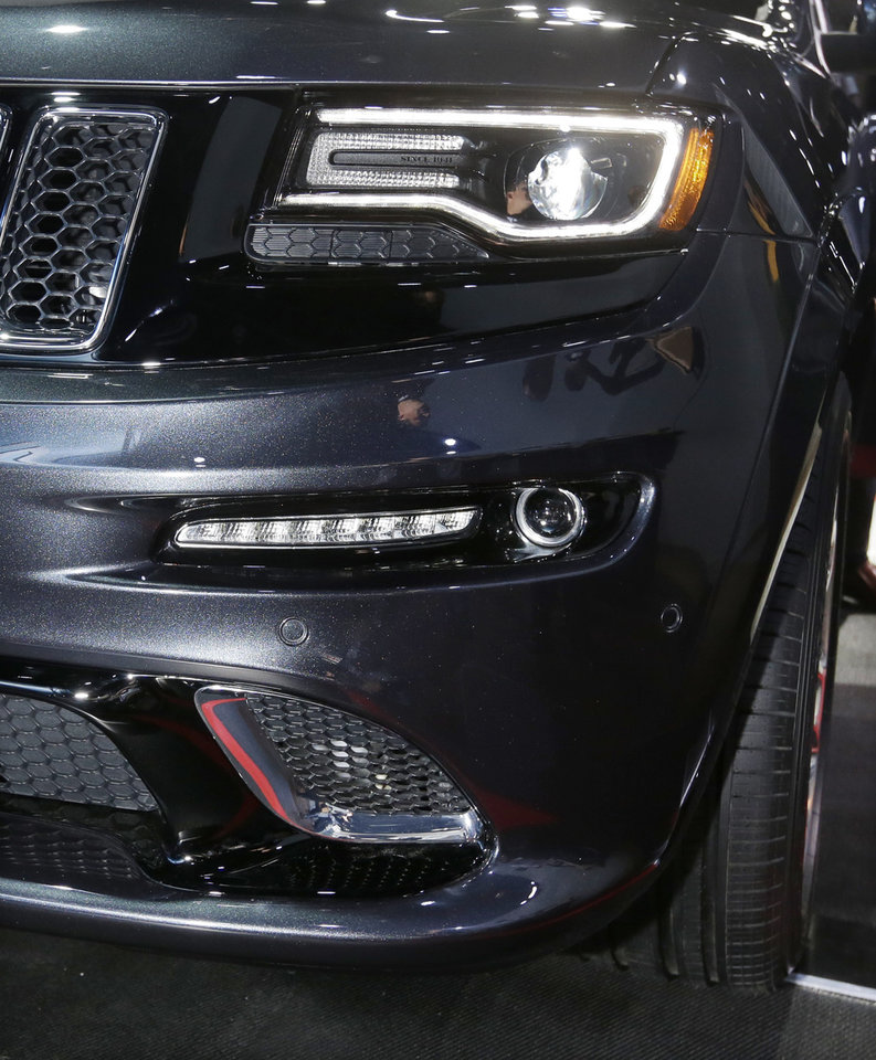 Photo - The front lamps on the high-performance SRT version of the 2014 Jeep Grand Cherokee are seen at the North American International Auto Show in Detroit, Tuesday, Jan. 15, 2013. The lamps are tinted black, giving it a distinct look. Ralph Gilles, a Chrysler design leader who also is president and CEO of the SRT brand and motorsports, noted the vehicle has black