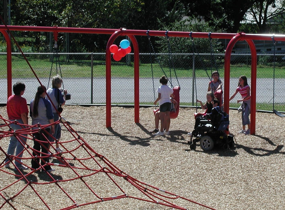 Unidentified Choctaw Elementary students enjoy the fully accesible swings installed during Phase II of the project.<br/><b>Community Photo By:</b> Oklahoma County District One<br/><b>Submitted By:</b> joe, norman