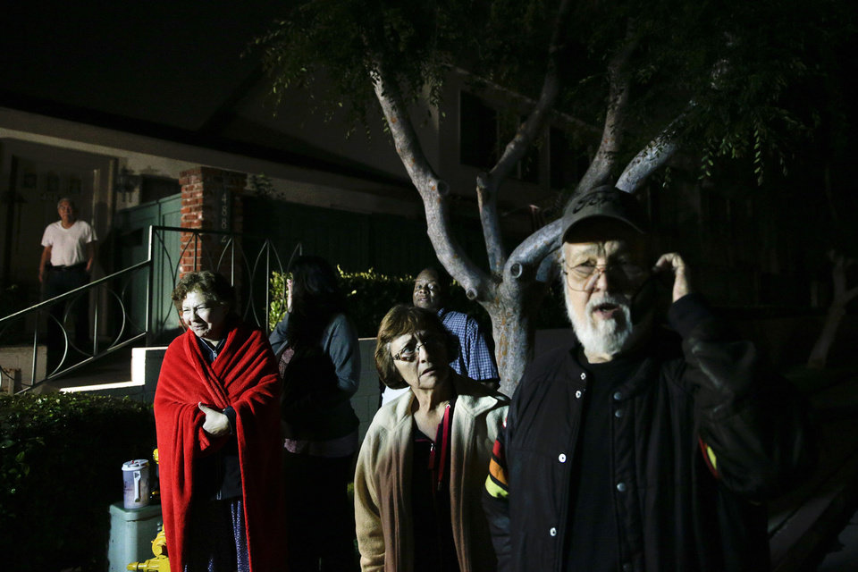 Photo - Larry Van Osten, right, talks on the phone as he and other residents stand outside their condo complex during a power outage caused by an earthquake on Friday, March 28, 2014, in Buena Park, Calif. A magnitude-5.1 earthquake was widely felt in the Los Angeles area and surrounding counties Friday evening, but authorities said there were no immediate reports of significant damages or injuries. (AP Photo/Jae C. Hong)