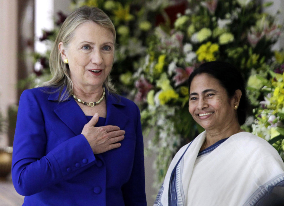 Photo -   U.S. Secretary of State Hillary Rodham Clinton, left, gestures beside West Bengal Chief Minister Mamata Banerjee before a meeting in Kolkata, India, Monday, May 7, 2012. Clinton met with Mamata Banerjee, a key partner of India's ruling coalition who has stymied government efforts to lift restrictions on foreign-owned investments in the country. (AP Photo/Bikas Das)