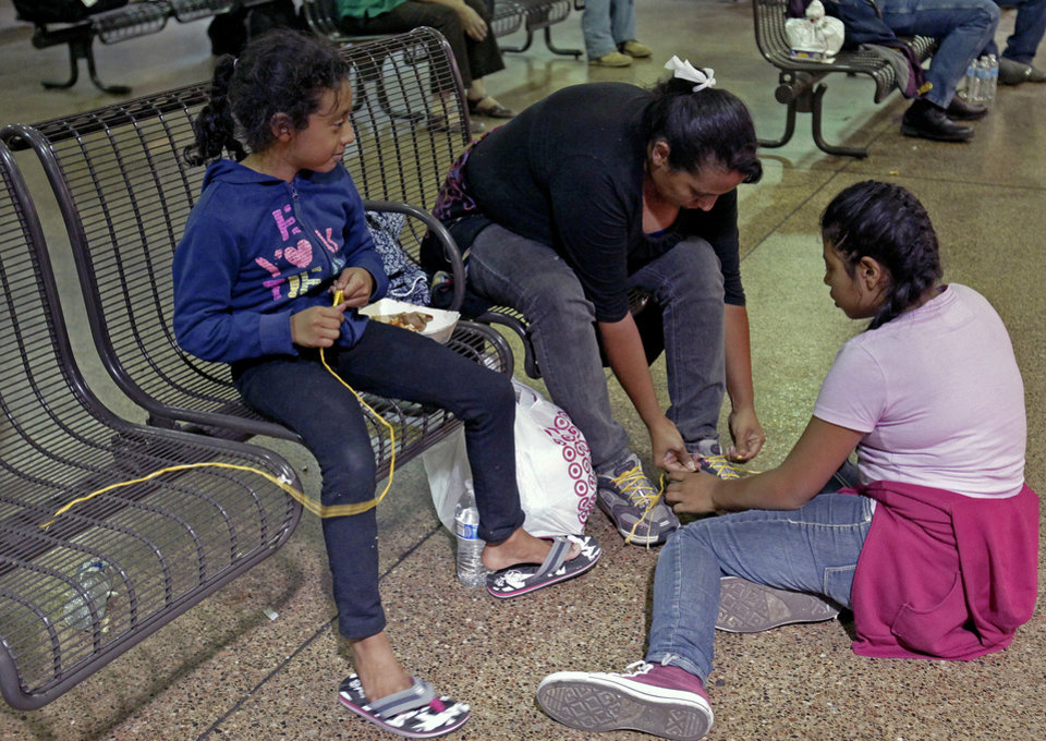 Photo - Elana Carmen, middle, with her daughters Abigail, right, and Ayala, of El Salvador, tie their shoes with yellow rope for shoe laces, Thursday, May 29, 2014 at the Greyhound bus terminal in Phoenix. About 400 mostly Central American women and children caught crossing from Mexico into south Texas were flown to Arizona this weekend after border agents there ran out of space and resources.  Officials then dropped hundreds of them off at Phoenix and Tucson Greyhound stations, overwhelming the stations and humanitarian groups who were trying to help. (AP Photo/Rick Scuteri)
