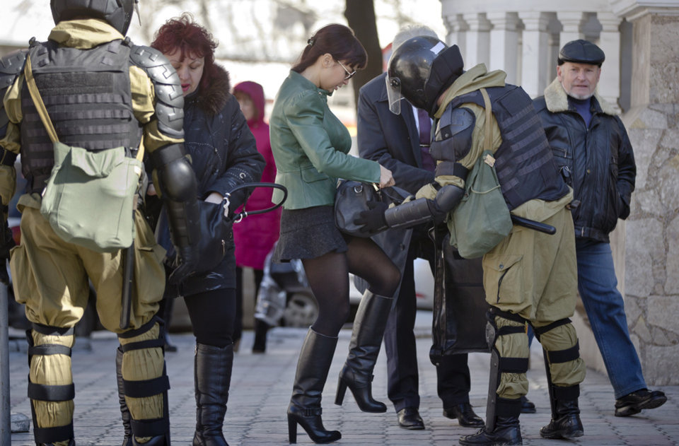 Photo - Women present their bags to armed men in riot gear, performing identity and hand bag checks on people walking near the building of Crimea's regional parliament in Simferopol, Ukraine, Monday, March 17, 2014. Crimea's parliament on Monday declared the region an independent state, after its residents voted overwhelmingly to break off from Ukraine and seek to join Russia. (AP Photo/Vadim Ghirda)