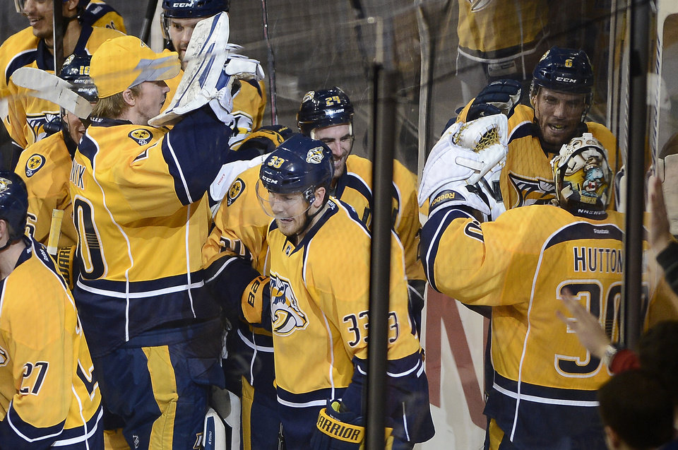Photo - Nashville Predators defenseman Shea Weber (6), upper right, celebrates with his team and goalie Carter Hutton (30) after scoring the winning goal in overtime against the New Jersey Devils at an NHL hockey game on Friday, Jan. 31, 2014, in Nashville, Tenn. (AP Photo/Mark Zaleski)