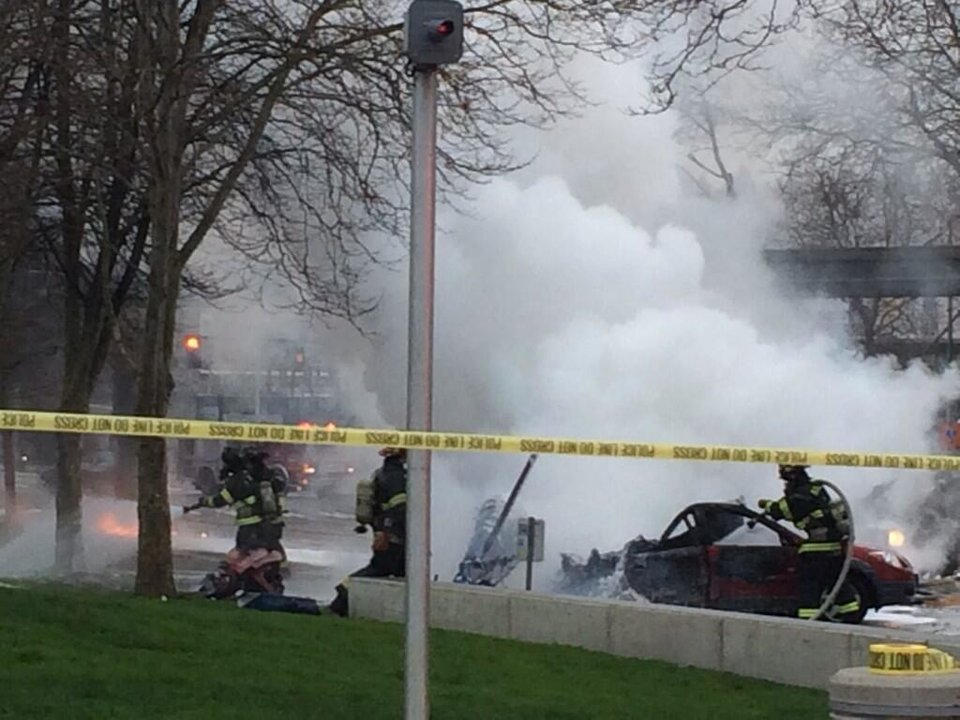 Photo - In this photo provided by KOMO-TV, emergency personnel respond to the scene of a helicopter crash outside the KOMO-TV studios near the space needle in Seattle on Tuesday, March 18, 2014. The station says the helicopter was apparently coming in for a landing on its rooftop Tuesday morning when it possibly hit the side of the building and went down, hitting several vehicles on Broad Street.  (AP Photo/KOMO-TV, Kelly Koopmans)
