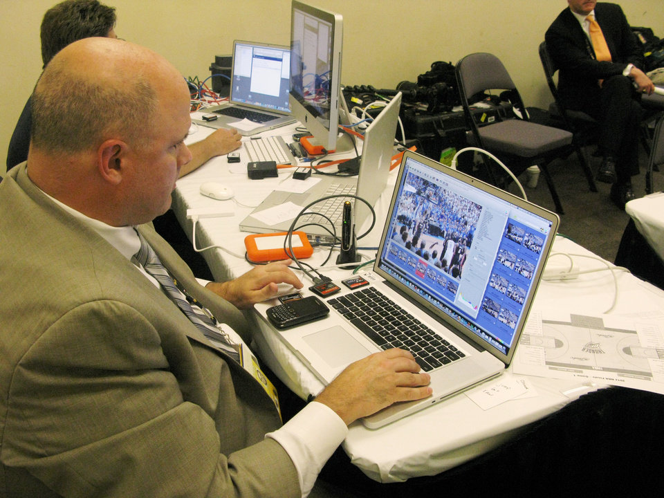Joe Amati, vice president of NBA Photos, clicks through photos he has just received from photographers in the arena as he decides which ones to send out right away for posting to the NBA's social media feeds like Twitter and Facebook. PHOTO BY LILLIE-BETH BRINKMAN, THE OKLAHOMAN. <strong></strong>