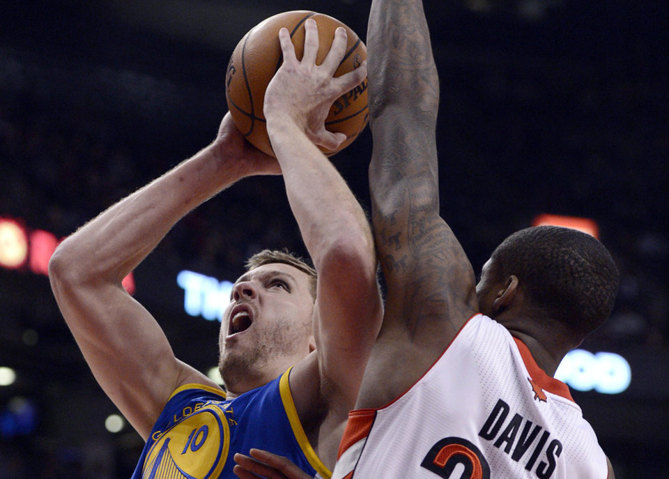 Golden State Warriors David Lee jumps past Toronto Raptors Ed Davis during NBA action in Toronto on Monday, Jan. 28, 2013.  (AP Photo/The Canadian Press, Frank Gunn)