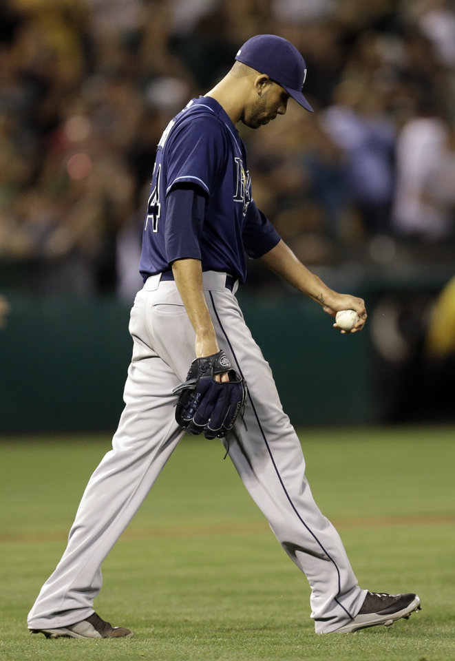 Photo - Tampa Bay Rays' David Price walks back to the mound after giving up a three run home run to Oakland Athletics' Kurt Suzuki in the fifth inning of a baseball game, Friday, Aug. 30, 2013, in Oakland, Calif. (AP Photo/Ben Margot)