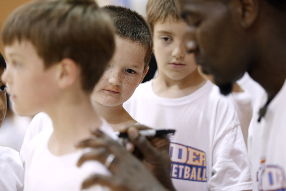 Davin Cargle looks on as Oklahoma City Thunder's Kendrick Perkins gives out autographs to participants in the Oklahoma City Thunder basketball camp at Mid-America Christian University on Wednesday, June 19, 2013 in Oklahoma City, Okla.   Photo by Chris Landsberger, The Oklahoman