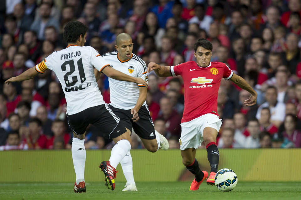 Photo - Manchester United's Reece James, right, fights for the ball with Valencia's Sofiane Feghouli, centre, and Dani Parejo during a pre-season friendly soccer match at Old Trafford Stadium, Manchester, England, Tuesday Aug. 12, 2014. (AP Photo/Jon Super)