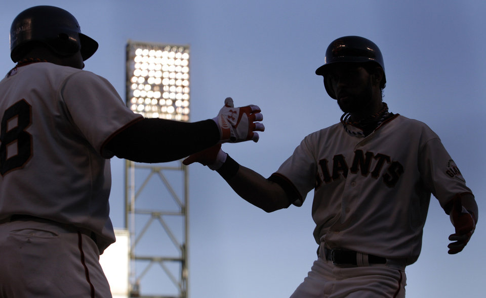 Photo -   San Francisco Giants' Angel Pagan, right, is congratulated by Pablo Sandoval after Pagan hit a home run during the first inning of Game 2 of baseball's National League championship series against the St. Louis Cardinals Monday, Oct. 15, 2012, in San Francisco. (AP Photo/Ben Margot)