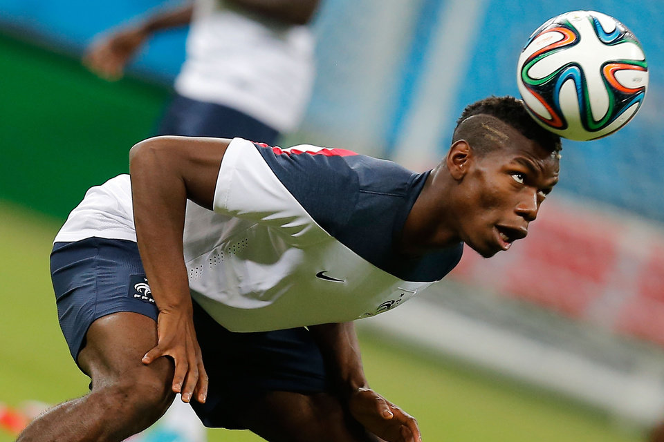 Photo - France's midfielder Paul Pogba heads the ball during an official training session the day before the group E World Cup soccer match between France and Switzerland at the Arena Fonte Nova stadium in Salvador, Brazil, Thursday, June 19, 2014. (AP Photo/David Vincent)