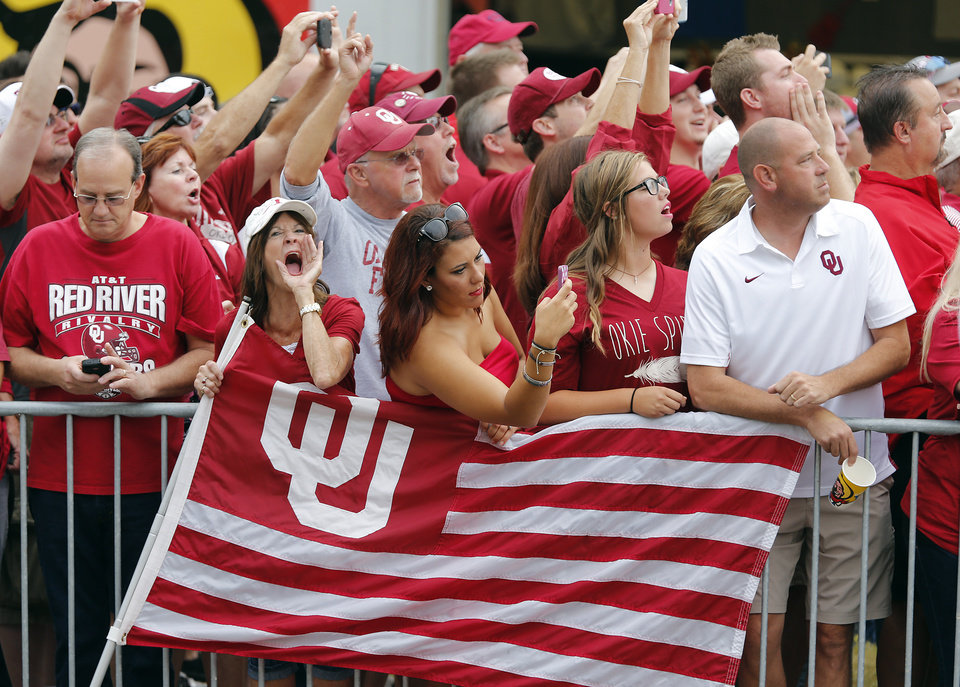 Photo - Oklahoma fans cheer as the Sooners arrive to the stadium during the Red River Rivalry college football game between the University of Oklahoma Sooners (OU) and the University of Texas Longhorns (UT) at the Cotton Bowl Stadium in Dallas, Saturday, Oct. 12, 2013. Photo by Chris Landsberger, The Oklahoman