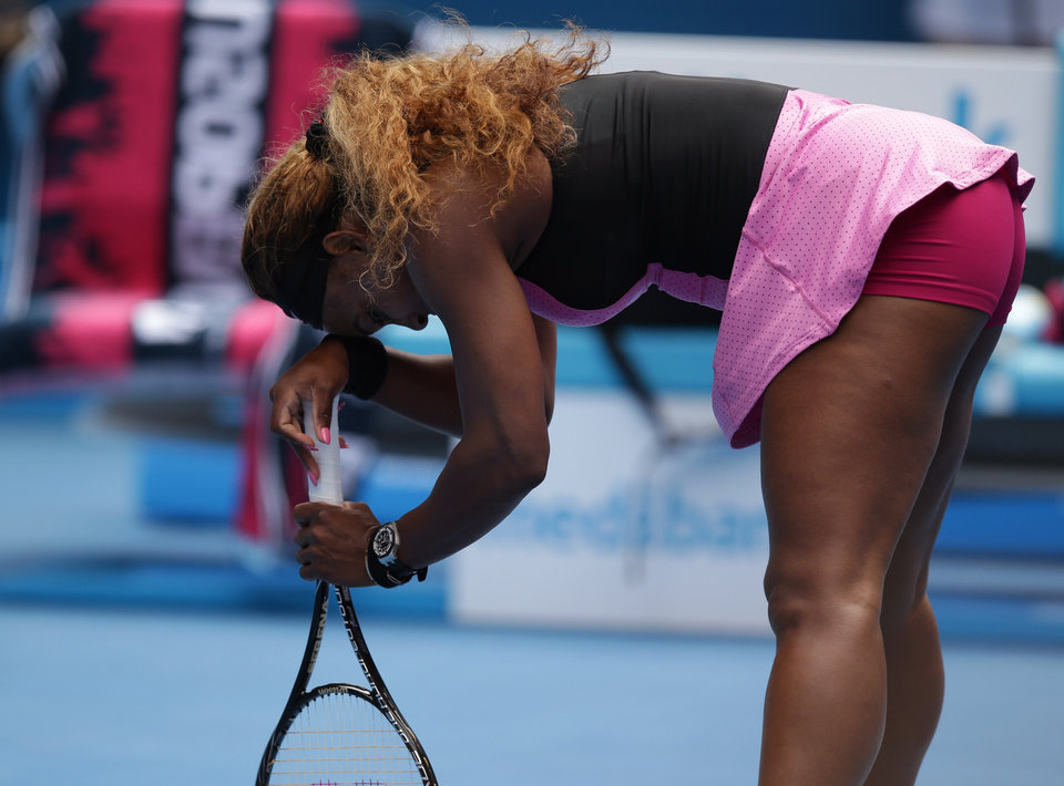 Photo - Serena Williams of the U.S. supports herself with a racket as she plays Ana Ivanovic of Serbia during their fourth round match at the Australian Open tennis championship in Melbourne, Australia, Sunday, Jan. 19, 2014.(AP Photo/Aaron Favila)