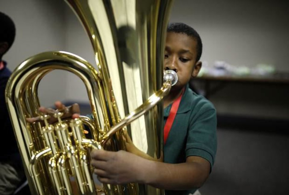 Photo - Gatewood Elementary School third-grader Malachi Lewis, 8, plays a tuba during a recent practice session for the El Sistema Oklahoma youth orchestra.  SARAH PHIPPS - The Oklahoman
