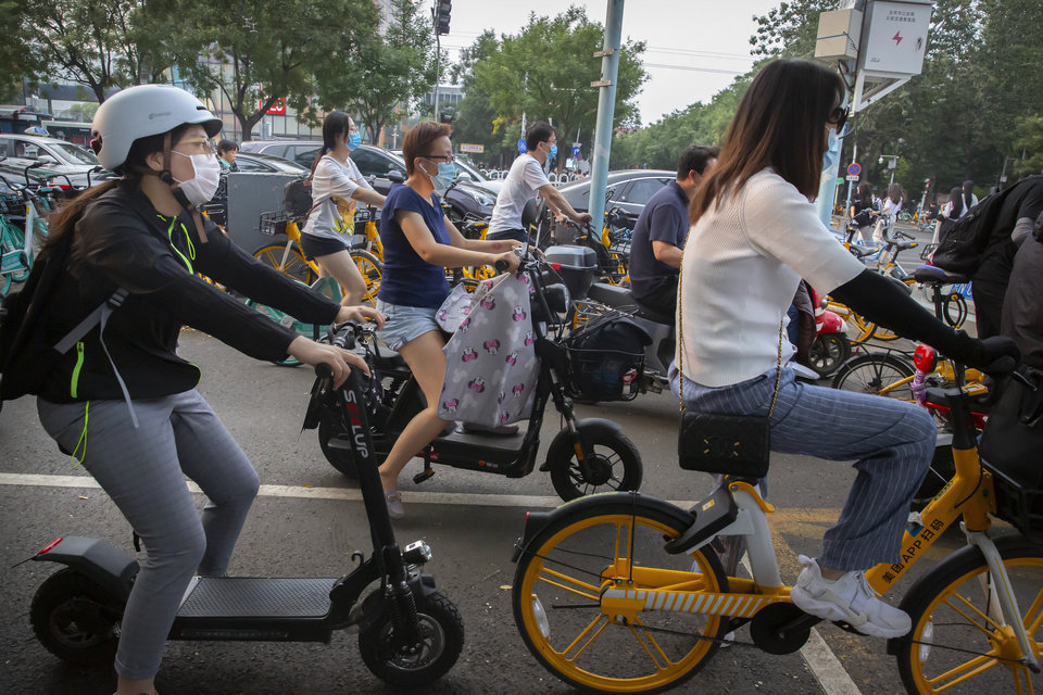 Photo -  People wearing face masks to protect against the coronavirus wait at an intersection in Beijing, Wednesday, July 29, 2020. China reported more than 100 new cases of COVID-19 on Wednesday as the country continues to battle an outbreak in Xinjiang. (AP Photo/Mark Schiefelbein)