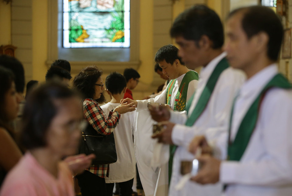 "CORRECTS MONTH- South Korean Catholic priest. Fr. Matthew Park, third from right, officiates during communion rites  at the Our Lady of Remedies Parish Church in Manila, Philippines Sunday, Sept. 22, 2013. Catholics around the globe are expressing mixed but mostly positive reactions to Pope Francis' recent remarks that the church has become too focused on ""small minded rules"" on hot-button issues like homosexuality and abortion. (AP Photo/Aaron Favila)"