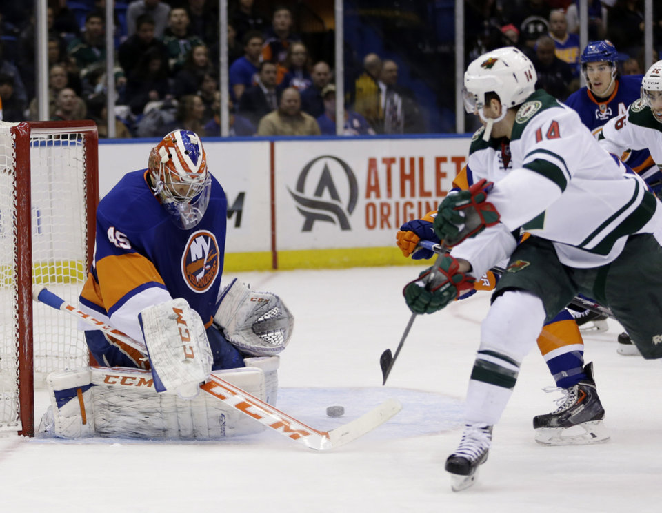 Photo - New York Islanders goalie Anders Nilsson, left,  makes a save during the first period of the NHL hockey game against the Minnesota Wild, Tuesday, March 18, 2014, in Uniondale, New York. (AP Photo/Seth Wenig)