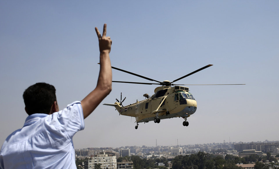 Photo - A man flashes a victory sign at an Egyptian military helicopter as it flies over the presidential palace in Cairo, Egypt, Friday, July 26, 2013. Political allies of Egypt's military lined up behind its call for huge rallies Friday to show support for the country's top general, Abdel-Fattah el-Sissi,  pushing toward a collision with Islamist opponents demanding the return of Mohammed Morsi, the nation's ousted president. (AP Photo/Hassan Ammar)