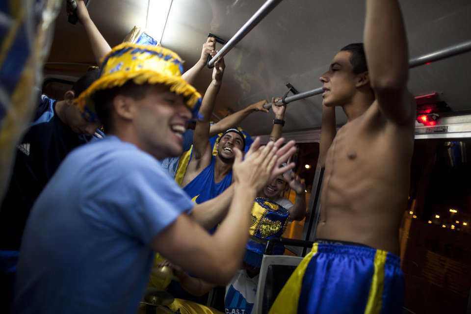 "Members of the murga ""Los amantes de La Boca"" have fun on a bus as they head to carnival celebrations in Buenos Aires, Argentina, Saturday, Feb. 2, 2013. Argentina�s carnival celebrations may not be as well-known as the ones in neighboring Uruguay and Brazil, but residents of the nation�s capital are equally passionate about their �murgas,� or traditional musical troupes. The murga ""Los amantes de La Boca,� or �The Lovers of The Boca� is among the largest, with about 400 members. It�s a reference to the hometown Boca Juniors, among the most popular soccer teams in Argentina and the world. (AP Photo/Natacha Pisarenko)"